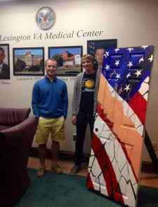 Nathan Williams, left, and John Thompson of Art in Unlikely Places delivered artist Cameron White's door to the Lexington Veterans Affairs Medical Center. (Photo from UKNow)