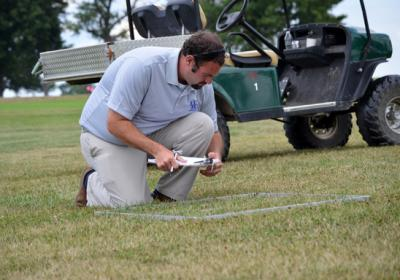 UK doctoral student Kenneth Cropper takes measurements in one of the lawn management systems at UK Spindletop Research Farm. (Photo by Katie Pratt)