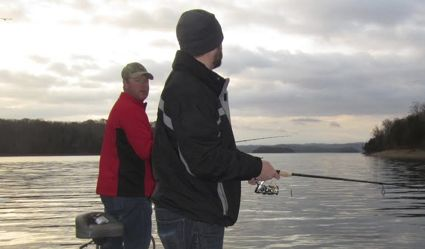 Chad Miles (left) and his brother Matt fish Dale Hollow Lake last December. The darkening clouds in the background portend the coming low barometric pressure front that prompted a morning of productive early winter fishing for smallmouth bass. This scenario is one of the best weather patterns for productive fishing (F&W Photo)