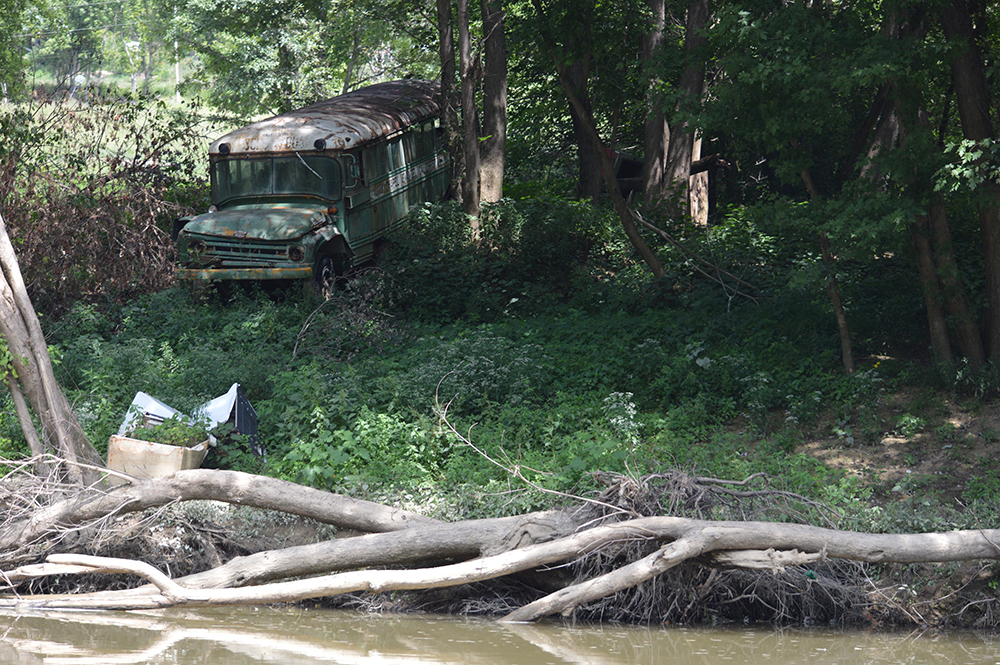 An abandoned bus slowly succumbs to years of neglect on the bank of the Licking River (Photo by Andy Mead)