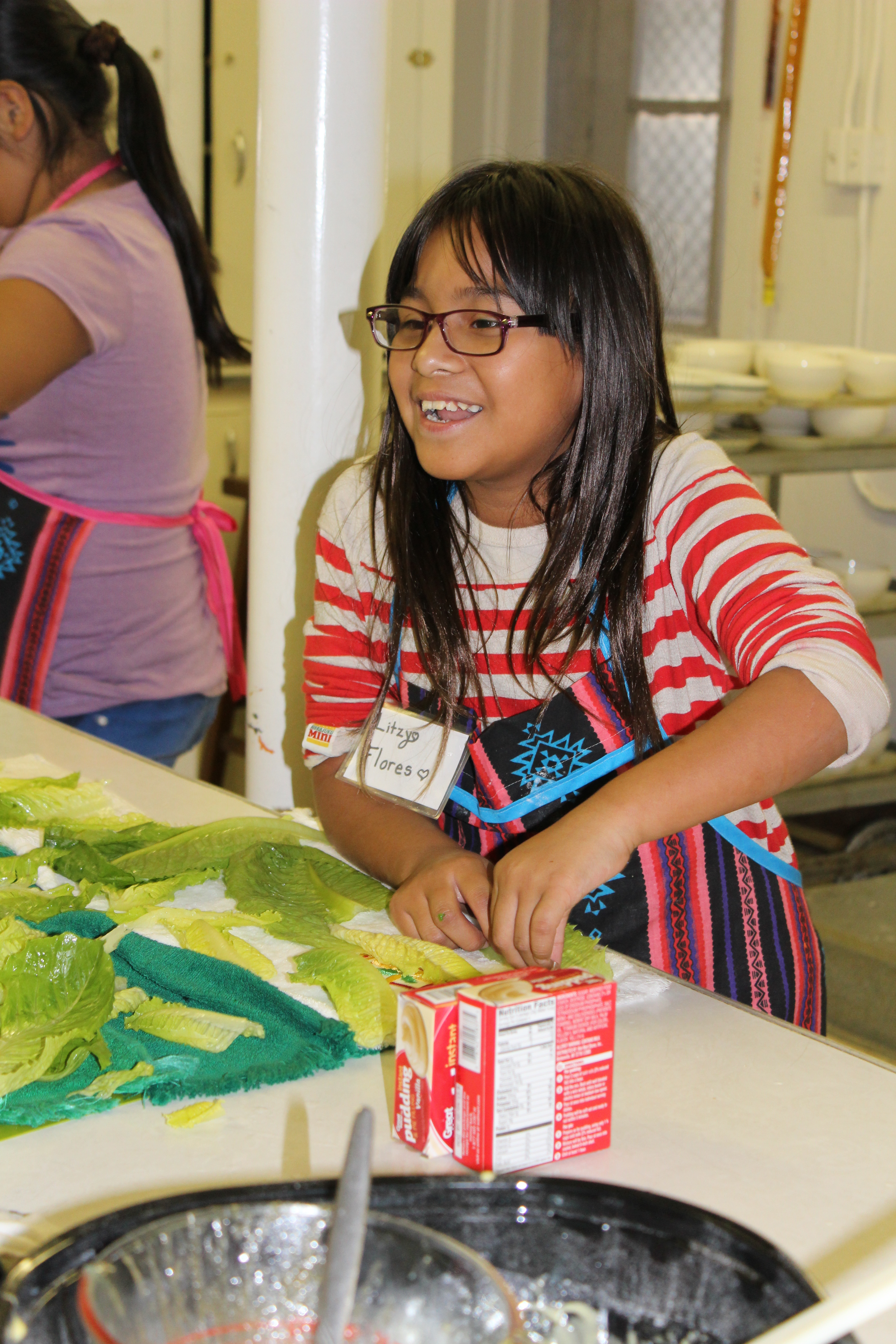 A Cooking Club student helps wash lettuce for a Caesar salad.