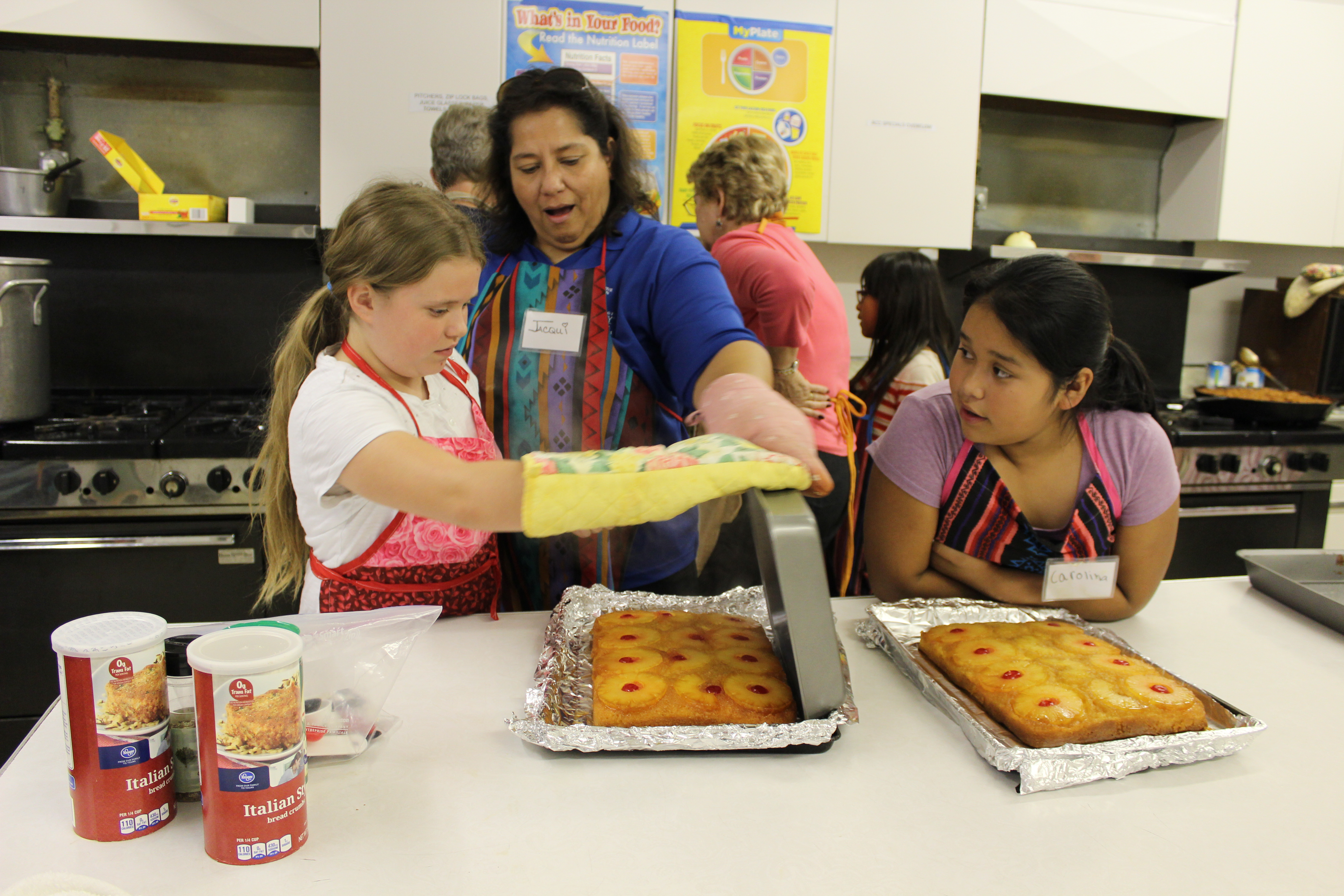 Jacqui Denegri, a nutrition educator with the Fayette County Extension Office, helped two girls flip the pineapple cakes hot out of the oven.
