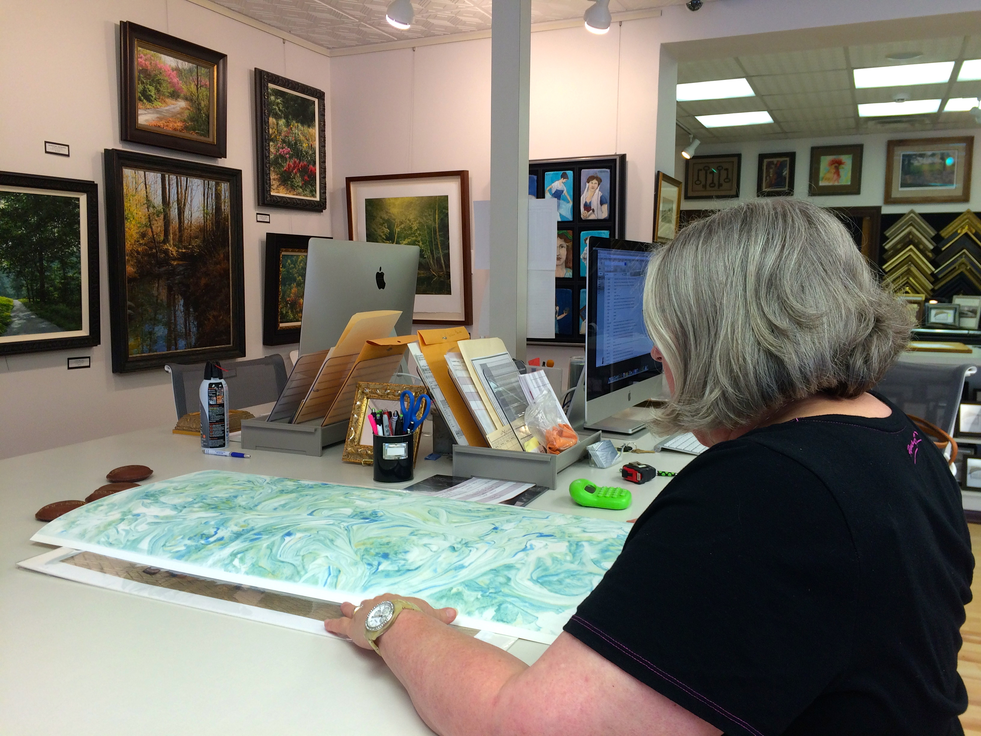 Letha Drury works with an original piece of art in preparation for framing. (Photo by Sydney Bland)