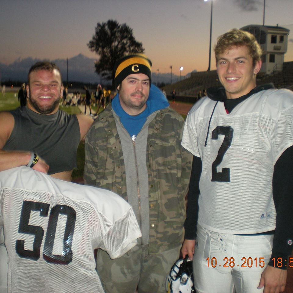 Football players Chuck Taylor and Blake Marin flank team manager Lindsay Baker.
