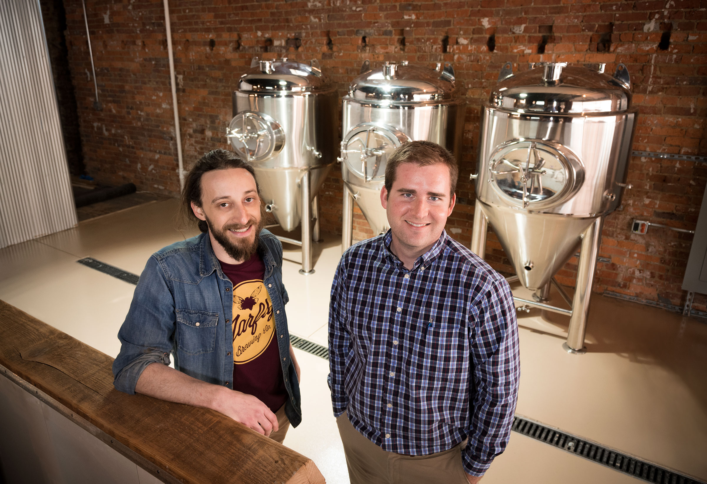 Jarfly Brewing owners Daniel Stroud, left, and Delaney Stephens in front of the four barrel fermentation system installed Sunday at the brewery, located on West Mount Vernon Street in Somerset. The building housed Somerset's premier furniture store, Goldenberg Furniture, for 105 years (Photo Provided)