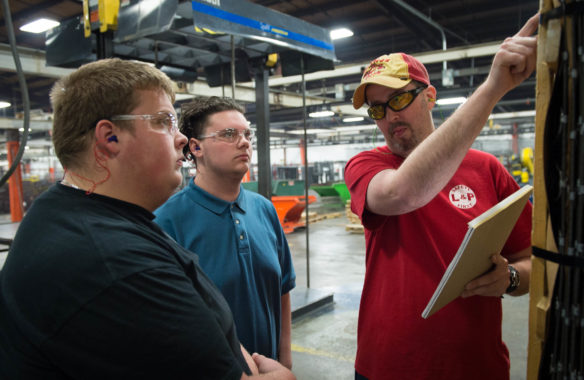 Jeff Fletcher, right, shows Brett Foley and Garrett Samuels what to look for while doing a quality inspection.  (Photo by Bobby Ellis)