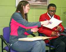 SkillsUSA club advisor Chelsea Mobley, left, helps one of her students with skill sets. (Photo from FCPS)