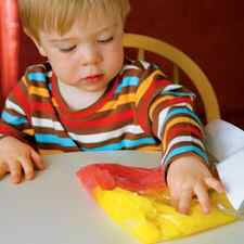 This child is using cornstarch, sugar, water and food coloring in Ziploc bags to enjoy mixing and mashing the colors. (Photo by Kelly Fagen on familyfun.go.com)