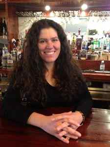 Amelia Kirby is shown behind the bar at Summit City. (Photo from Daily Yonder)