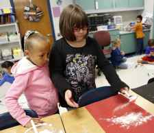 """Amiyah Simpson and Danielle Watts shake their animal design to see how much """"pollen"""" will trasfer off of it during Debbie Lewis' 2nd-grade class at Morningside Elementary School in Elizabethtown. (Photo by Amy Wallot)"""
