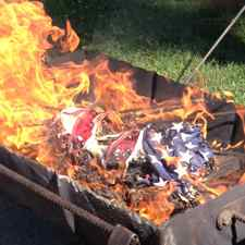 American flags are burned until they are completely ash and unrecognizable.