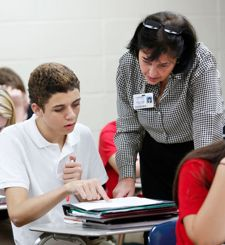 Sharon Graves helps 8th-grade student Kobe Peterson with an assignment about the Columbian Exchange – the transfer of animals, plants, culture and diseases to and from the New World. (Photo by Amy Wallot)