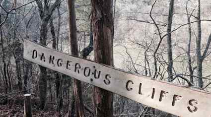 """At Dupree Preserve's overlook, a sign warns of """"Dangerous Cliffs."""" Author's collection."""