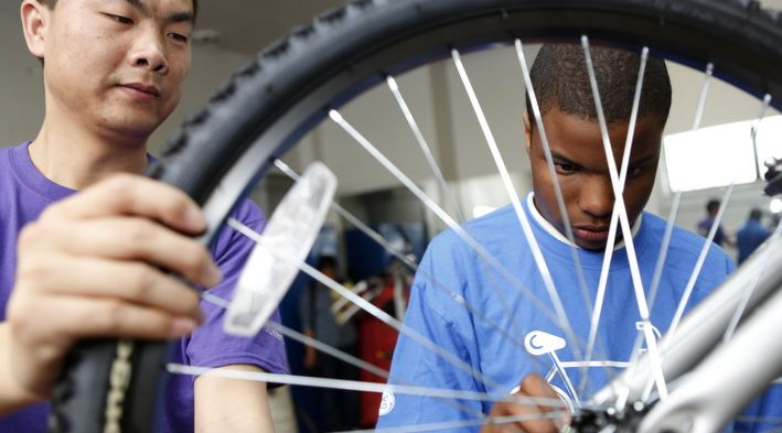 Volunteer Fang Ping holds the wheel steady as 7th-grade student Elijah Crosby tightens the bolts during the bike club at Holmes Middle School bike club. Crosby said being in the club has boosted his courage and confidence. (Photo by Amy Wallot)