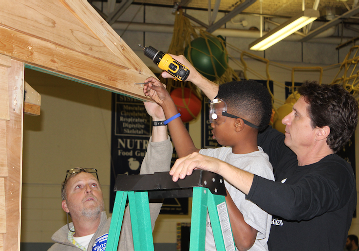 Under close supervision, students hoisted precut sheets of plywood, boards, windows, and the front door; they learned to handle cordless drills and hammers; and they practiced safety first with stepladders and goggles. (Photos by Tammy L. Lane)