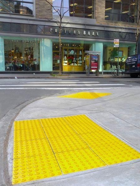 These ground surface indicators are designed to help people with a visual impairment determine the boundary between a sidewalk and a street, where there is no curb to warn them (Wikimedia Photo)