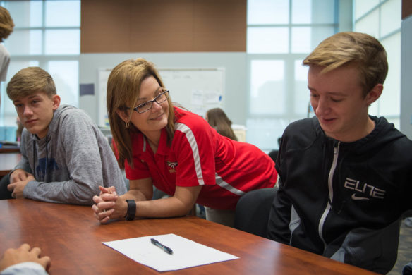 Jake Keys, right, a sophmore at Bullitt East High School, discusses a business plan with teacher Amanda Comstock (Photo by Bobby Ellis)
